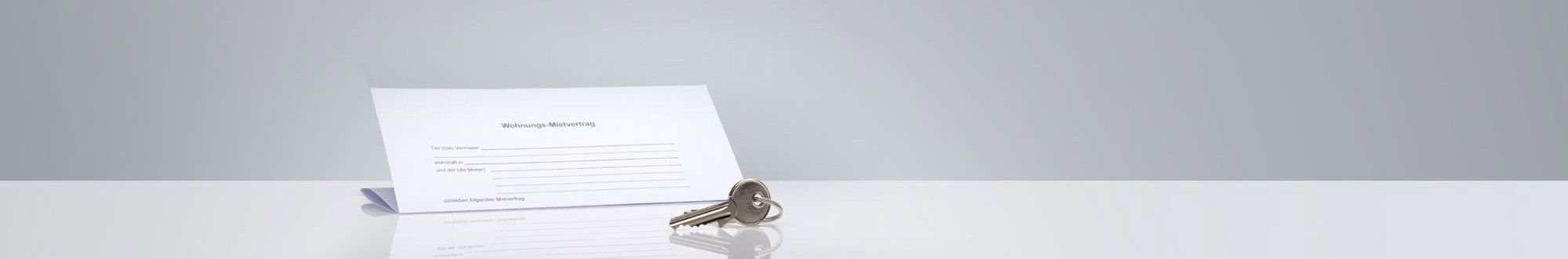 Mietvertrag und Schlüssel auf grauem Grund